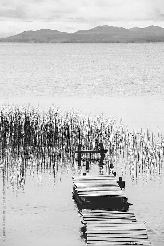 Wood dock on a lake by Alejandro Moreno de Carlos for Stocksy United