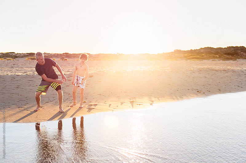 Father teaching his son how to skip stones at the beach at sunset by Angela Lumsden for Stocksy United