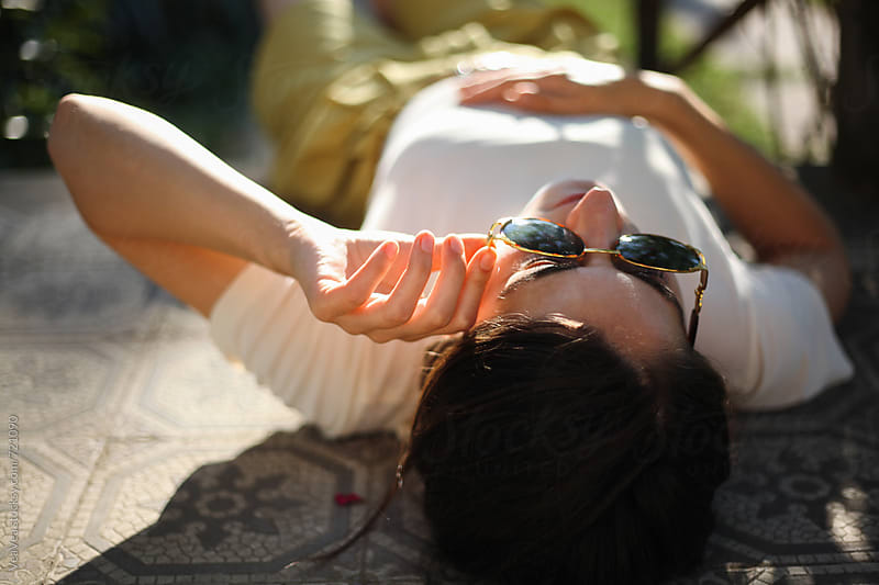 Young woman lying on the ground enjoying the Sun  by VeaVea for Stocksy United