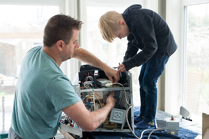 Father and Son Repairing Broken Microwave Oven Appliance At Home In Kitchen by JP Danko for Stocksy United