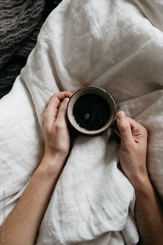 Two hands holding a mug of coffee on a white bedspread by KATIE + JOE for Stocksy United