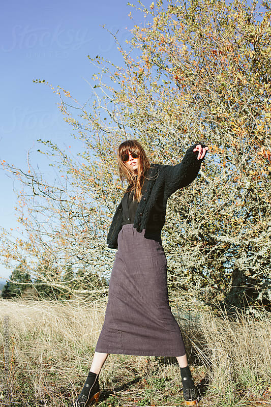 Woman dancing in a sunny field wear a skirt and sunglasses by KATIE + JOE for Stocksy United