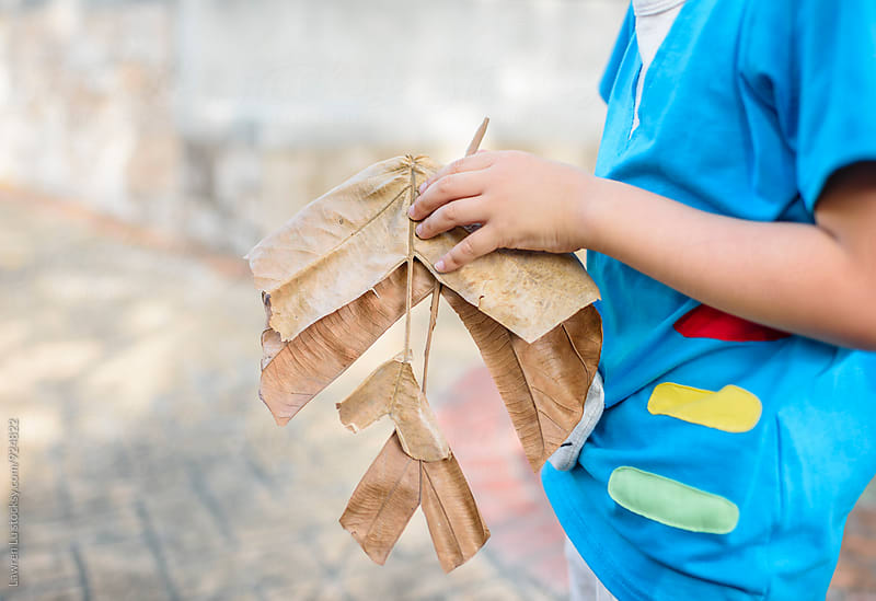 Kid holding airplane shape dried leaf by Lawren Lu for Stocksy United