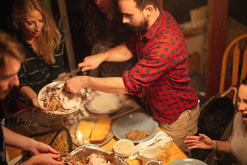 A group of friends eating at a holiday party by HOWL for Stocksy United