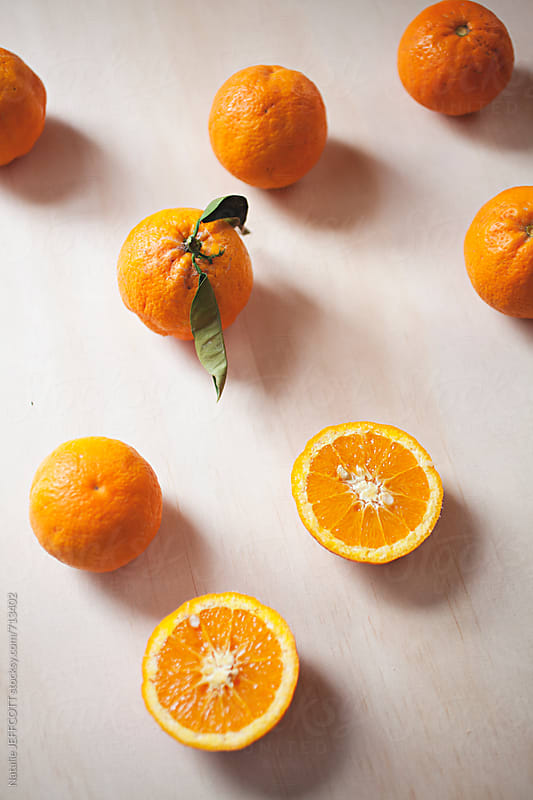 Fresh, organic, oranges picked from the tree on plywood table top by Natalie JEFFCOTT for Stocksy United