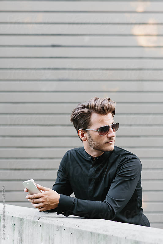 Handsome young man holding his mobile phone by Amir Kaljikovic for Stocksy United