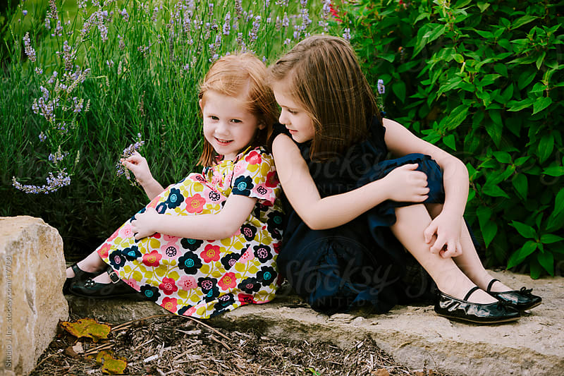 Little Girl Sisters Sit Back to Back Outside by Studio J, Inc. for Stocksy United