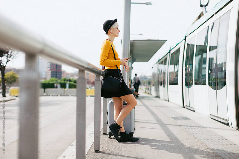 Modern woman using her smartphone standing on the train station. by BONNINSTUDIO for Stocksy United