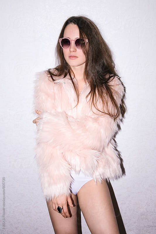 Young woman in faux fur coat posing against of white background by Danil Nevsky for Stocksy United