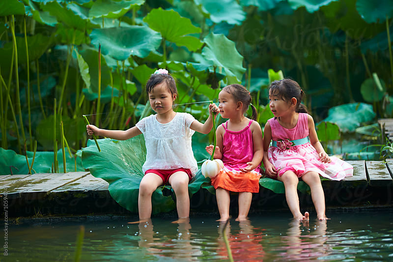Three little girls sitting by the pond playing water by cuiyan Liu for Stocksy United