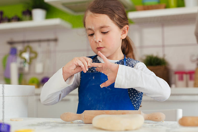 Little baker playing with dough. by Dejan Ristovski for Stocksy United