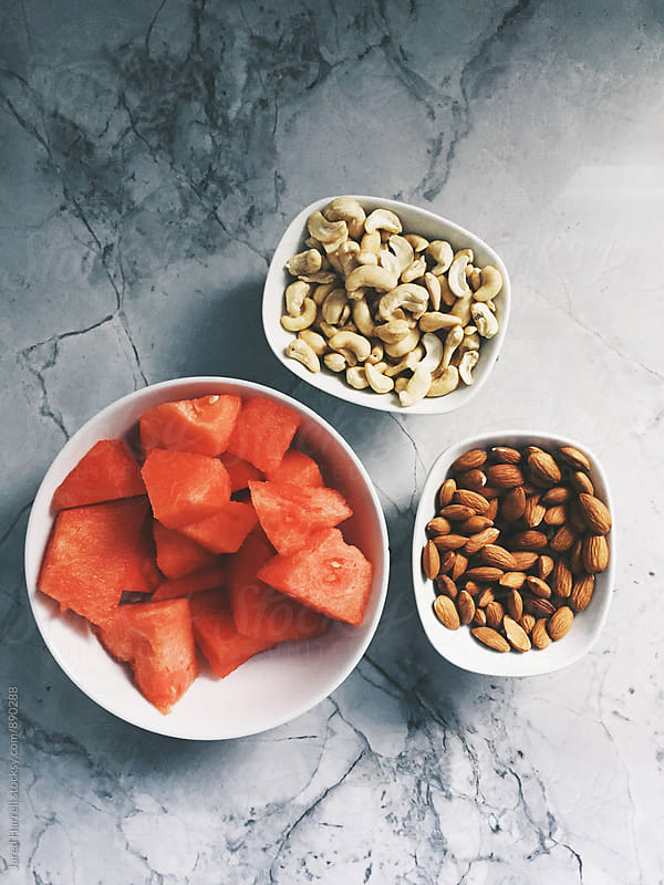 Bowls of Watermelon, Cashews, and Almonds on Marble Countertop by Jared Harrell for Stocksy United