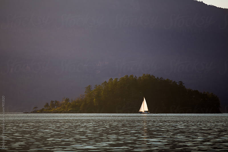 Sailboat reflecting in water with mountainous background by Christian Tisdale for Stocksy United