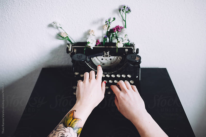 woman typing with a vintage typewriter  by Thais Ramos Varela for Stocksy United