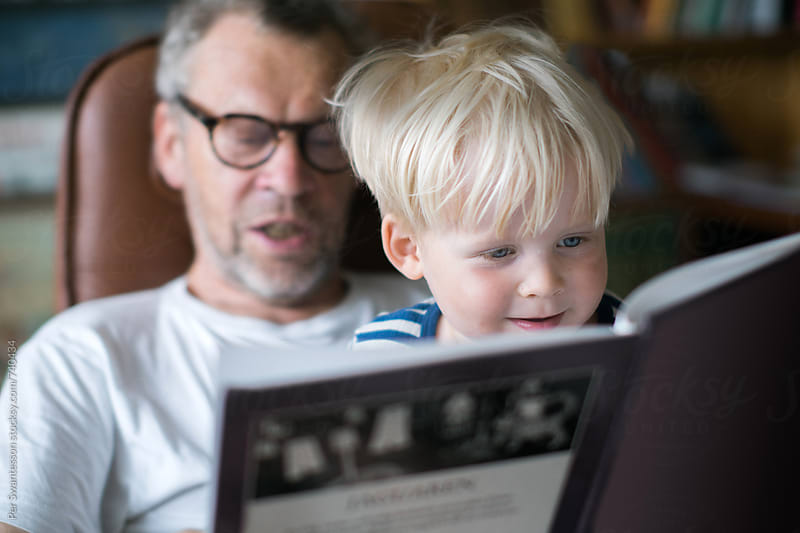 Grandfather reading a book with his toddler grandson by Per Swantesson for Stocksy United