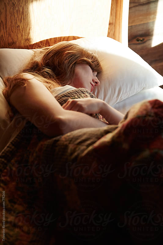 Woman sleeping in bed inside cabin by Trinette Reed for Stocksy United