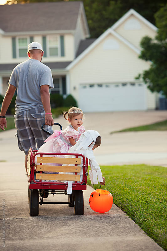 Halloween: Dad Pulls Kids In Wagon Trick-Or-Treating by Sean Locke for Stocksy United