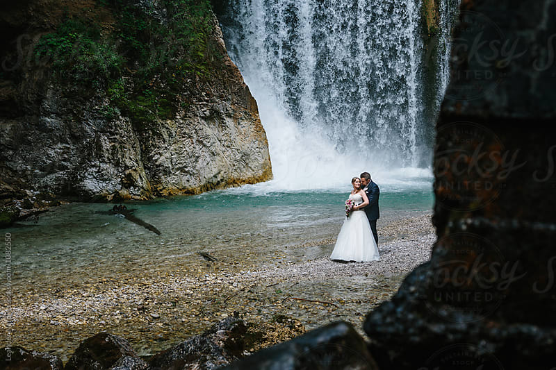 loving bridal couple standing  in front of a big waterfall on a rocky beach by Leander Nardin for Stocksy United