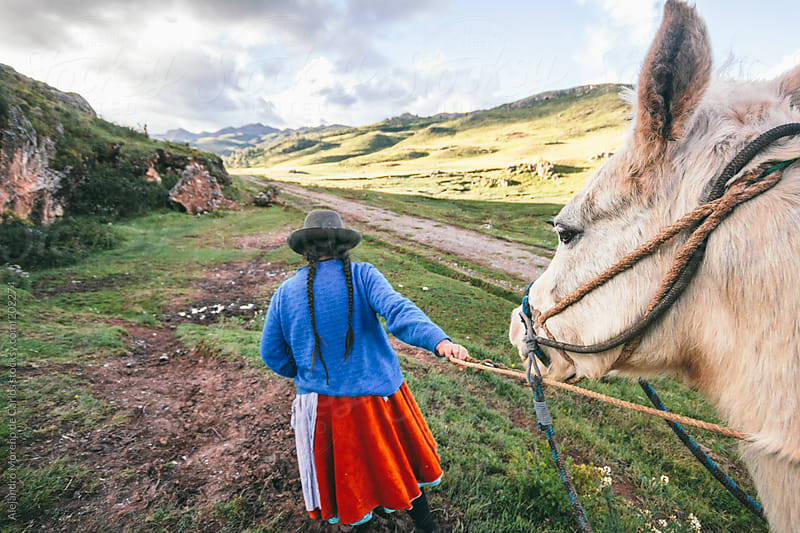 Horse riding and traditional cholita woman in Peru, South America travel by Alejandro Moreno de Carlos for Stocksy United