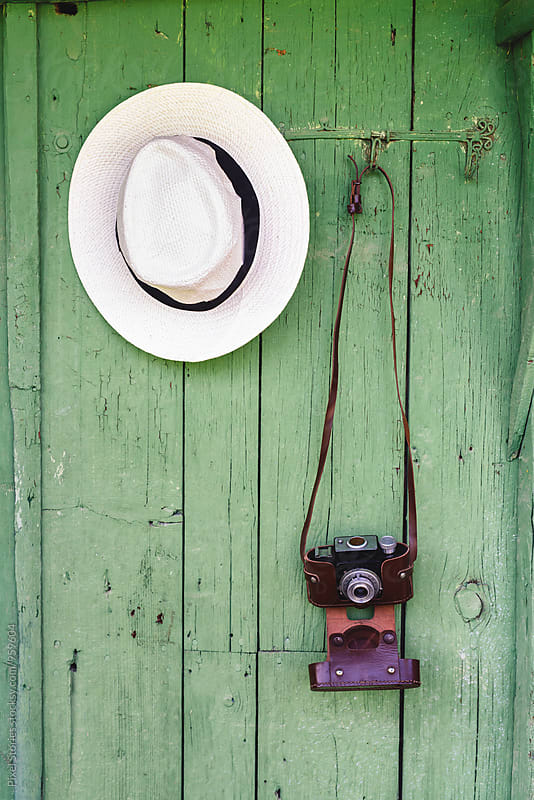 Vintage film camera and hat on green wall hanger by Pixel Stories for Stocksy United