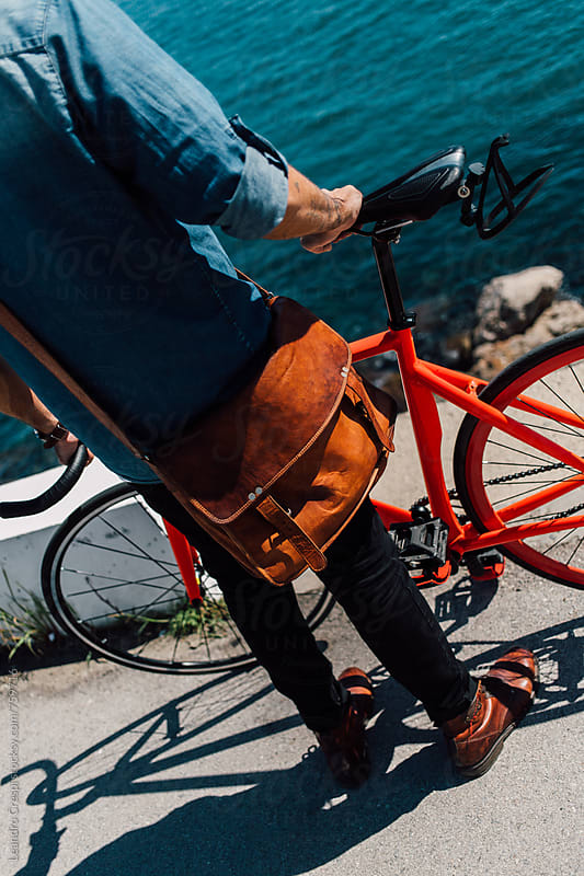 Man standing with a bicycle by Leandro Crespi for Stocksy United