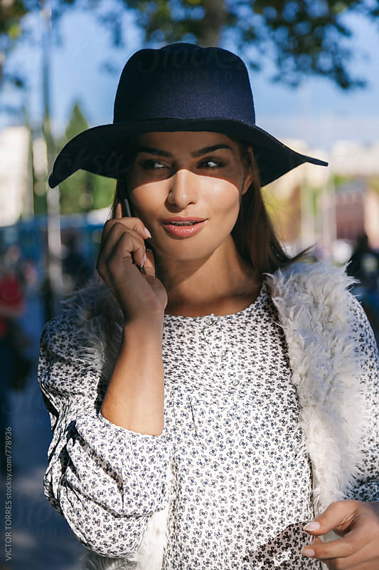 Cute Trendy Woman Talking By Phone in the Street by Victor Torres for Stocksy United