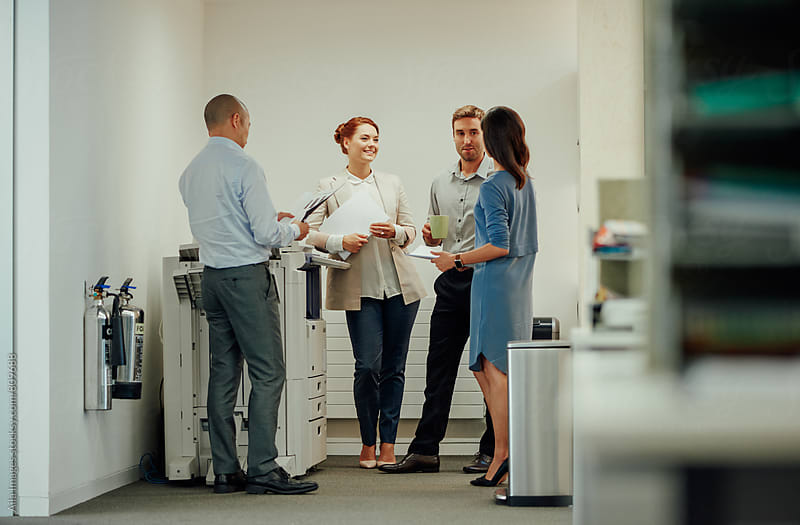 Young diverse business people interacting next to office photocopier by Aila Images for Stocksy United