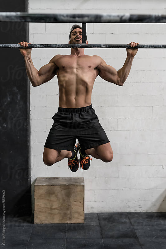 Man doing pull-ups in a gym by Guille Faingold for Stocksy United