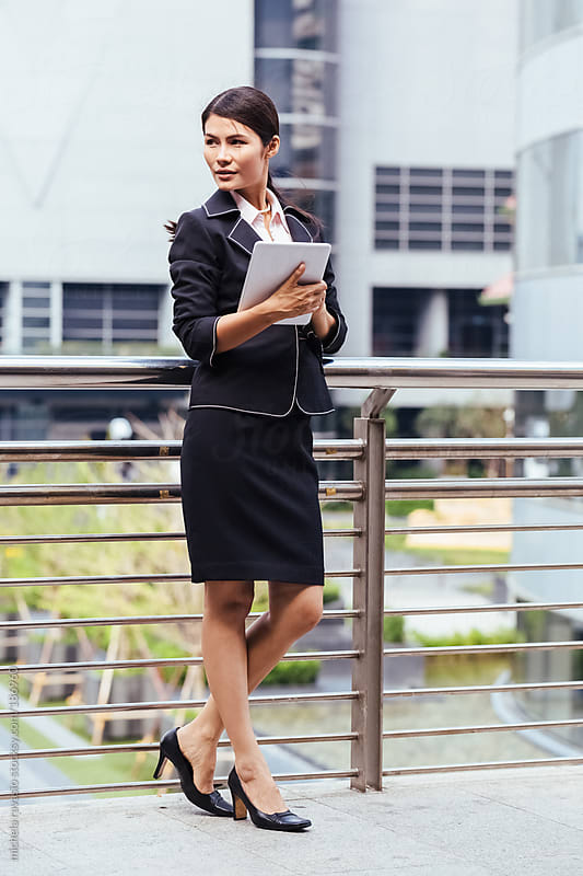 Business woman with digital tablet by michela ravasio for Stocksy United