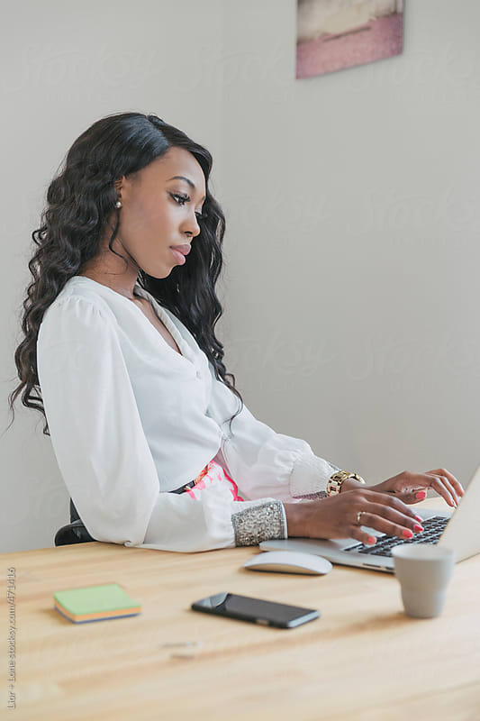Elegant black woman working on laptop in an office by Lior + Lone for Stocksy United