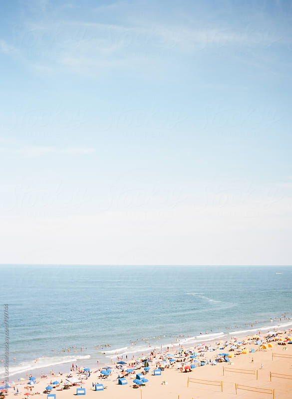 Distant view of beachgoers and the ocean by Marta Locklear for Stocksy United