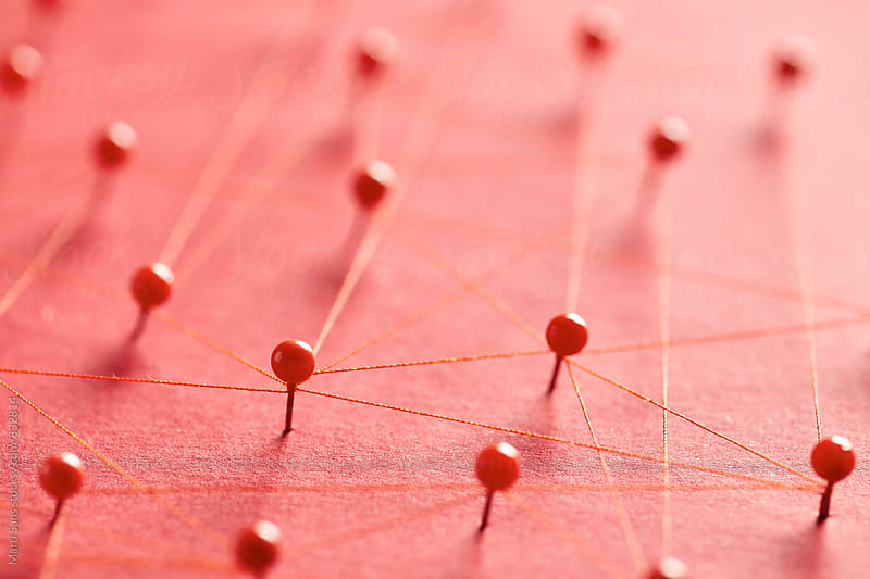 Red pins on pink background creating a network by Martí Sans for Stocksy United