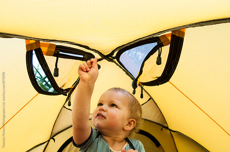 Girl toddler playing inside a tent while on a camping trip, New Zealand. by Thomas Pickard for Stocksy United