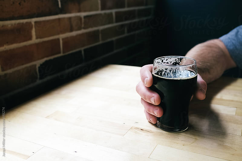 Man's hand holding a half pint of stout with copyspace - horizontal by Jacqui Miller for Stocksy United
