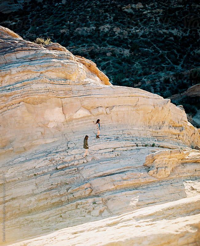 Two women walking on rocks by Daniel Kim Photography for Stocksy United