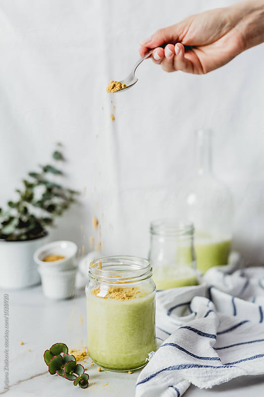 Melon smoothie with pollen by Tatjana Ristanic for Stocksy United