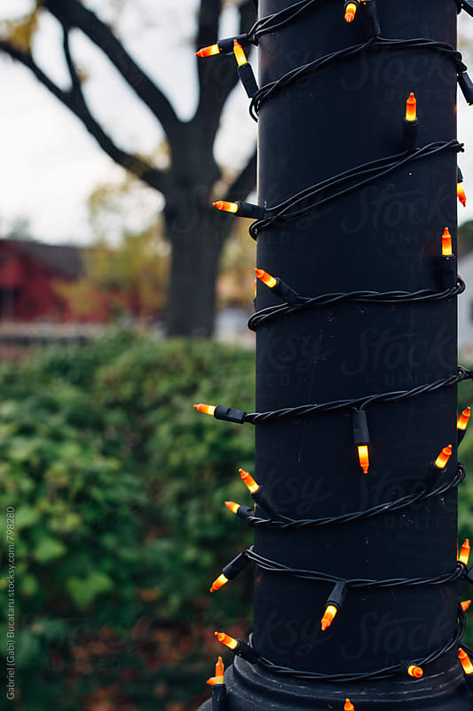 Lightpole wrapped with decorative candy corn Halloween lights by Gabriel (Gabi) Bucataru for Stocksy United
