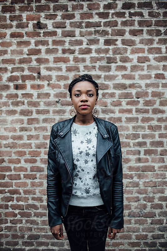 Portrait of young African woman against a brick wall by michela ravasio for Stocksy United