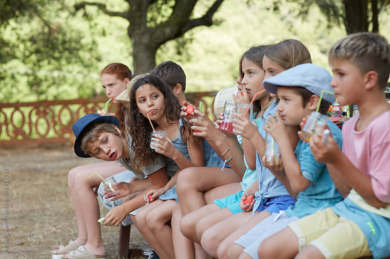 Group portrait of children  sitting on a bench and drinking by Miquel Llonch for Stocksy United