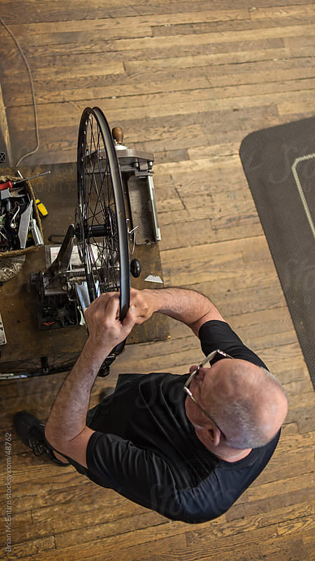 Local Bike Shop: Mechanic Truing Wheel, Overhead View by Brian McEntire for Stocksy United