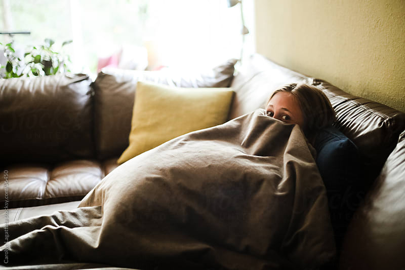 Young girl watching a scary movie and hiding under the blanket by Carolyn Lagattuta for Stocksy United