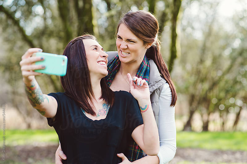 Cute lesbian couple taking a selfie in the park by Kate Daigneault for Stocksy United