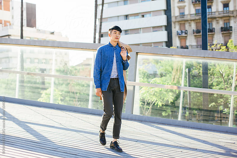 Stylish young asian man walking in the street. by BONNINSTUDIO for Stocksy United