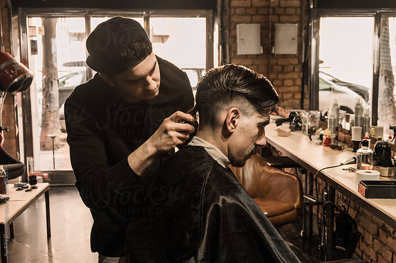 YOung barber working in vintage barber shop. by Marko Milanovic for Stocksy United