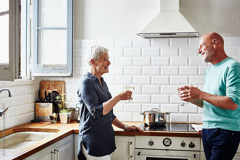 Happy Senior Couple Enjoying Wine In Kitchen by ALTO IMAGES for Stocksy United