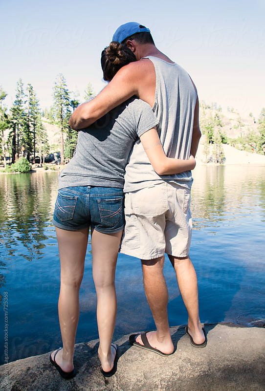 Father and daughter embracing by a lake in the Sierras by Carolyn Lagattuta for Stocksy United