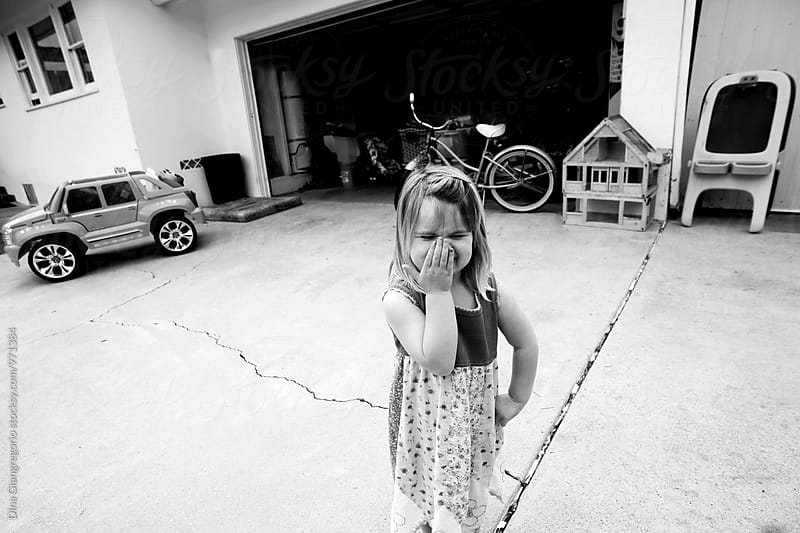 Little Girl Giggling On Front Driveway Of Her House With Toys Nearby by Dina Giangregorio for Stocksy United