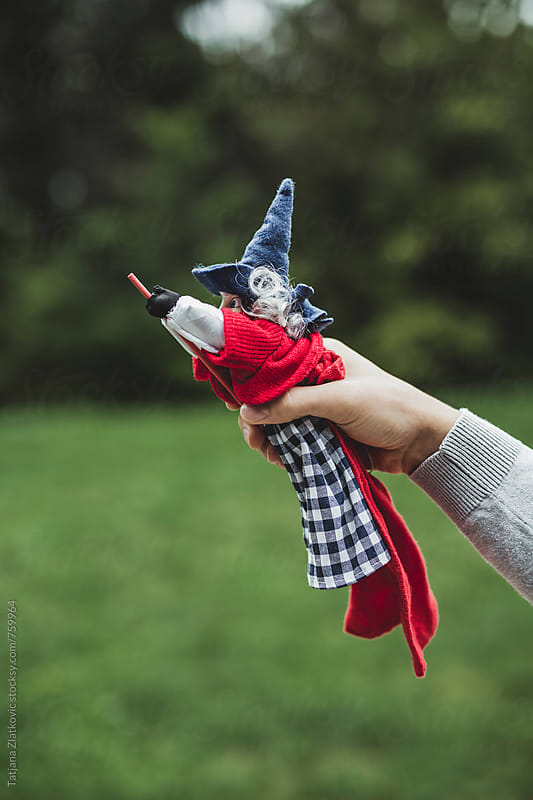 Hand holding witch toy by Tatjana Zlatkovic for Stocksy United