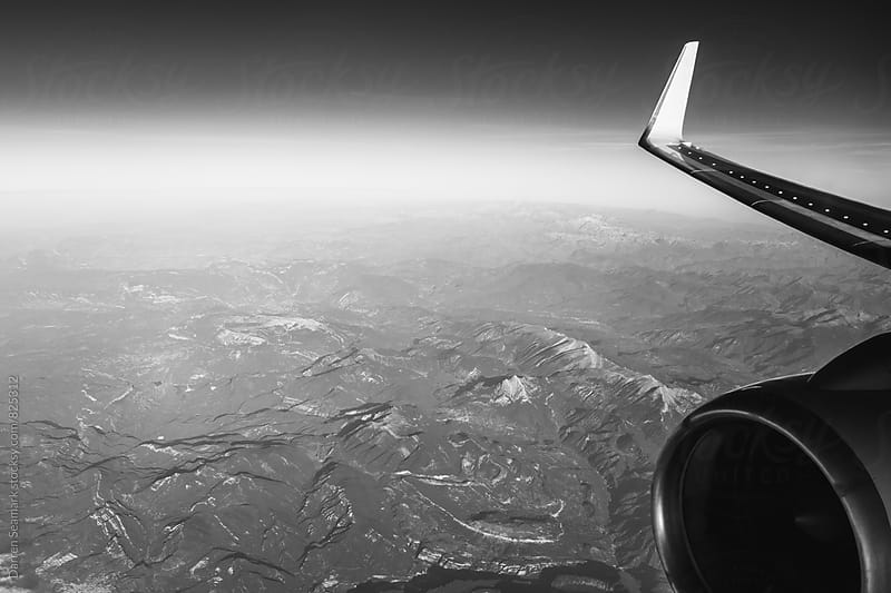 View of an aircraft wing and engine over a mountain range by Darren Seamark for Stocksy United