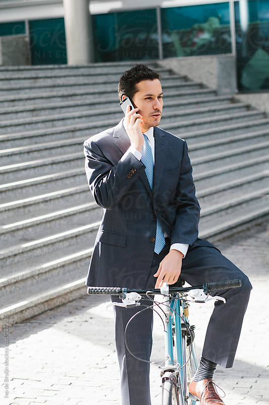 Young business man calling on the phone while sitting on his bike by Ivo de Bruijn for Stocksy United